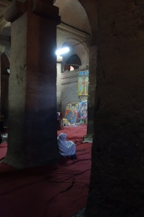 A worshiper in prayer inside Bet Medhane Alem.