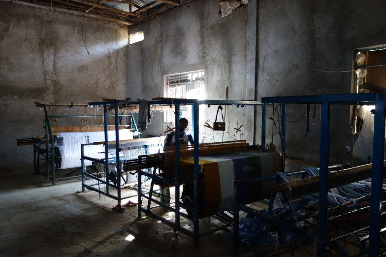 A man weaving in the textile factory.