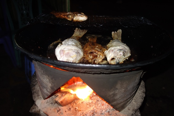Fresh tilapia being fried in a shack by the roadside.