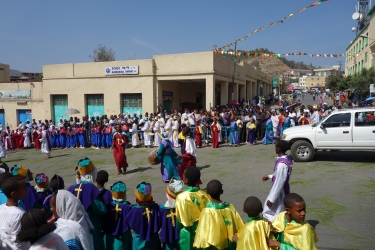 Children sing and dance in their uniforms.