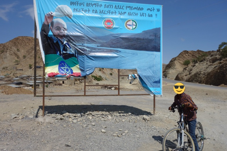 The boy on the bike was doing laps around town and asked me for a photo every time he passed me. In this one he begged me to take his picture next to this awkward banner of Meles Zenawi.