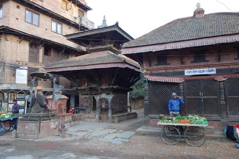 Produce vendor and a temple in the backstreets of Patan.