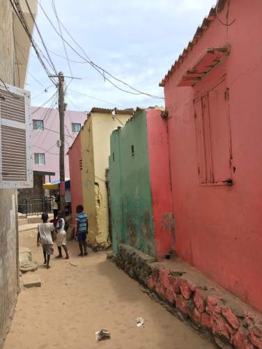 Children walk past colourful homes in Ngor.